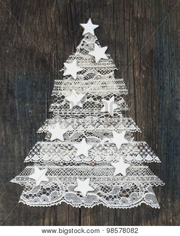 beautiful Xmas Tree made of delicate lace with decoration on the wooden background