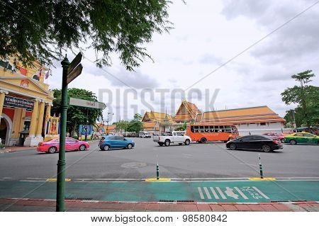 Traffic In Bangkok Near Wat Pho. The Color Of The Car On The Road And Colorful Temple