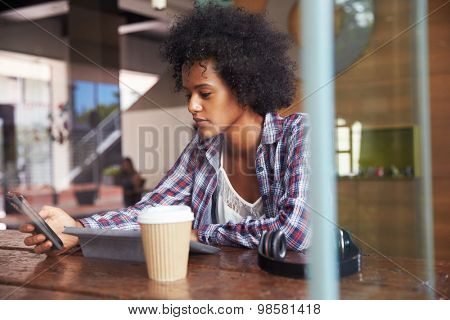 Businesswoman On Phone Using Digital Tablet In Coffee Shop