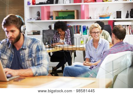 Businesspeople Having Informal Meeting In Busy Office