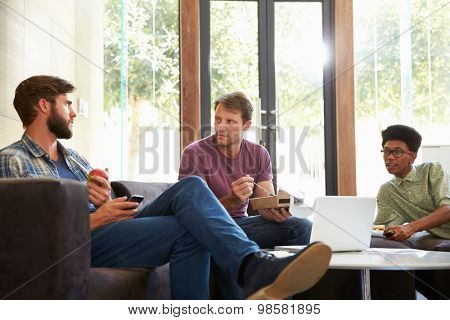 Three Businessmen Having Working Lunch In Office