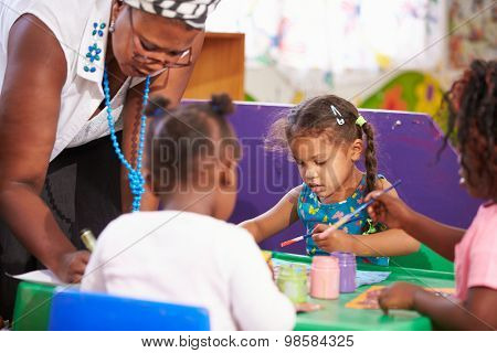 Teacher helping kids in a preschool class, close up