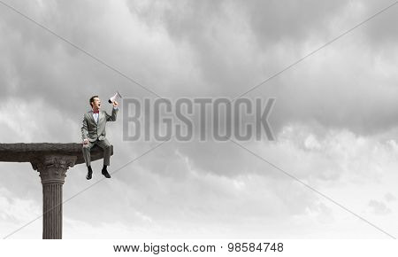 Businessman sitting on top edge and screaming in megaphone