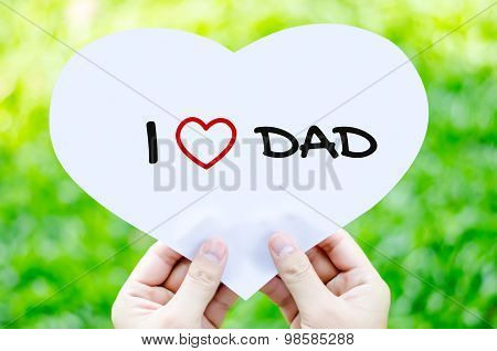 Hand Holding White Heart Paper With I Love Dad Text On Blur Green Grass Background - Father's Day