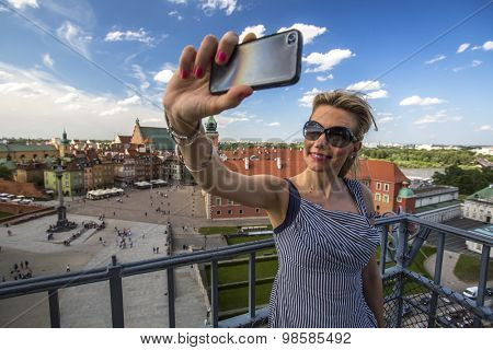 Young beautiful woman making selfie with smartphone on the background Warsaw Castle Square.