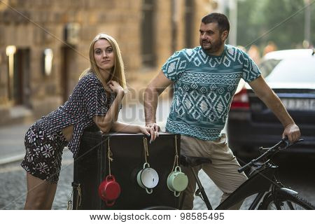Young couple on the street with vintage bike.