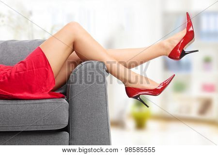 Close-up on female legs in red high heels lying on a gray couch indoors