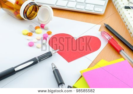 Health Care Concept - Red Heart With Supplement On Computer Desk