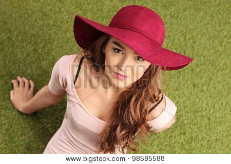 High angle shot of a cheerful young woman with a stylish hat sitting on grass and looking at the camera