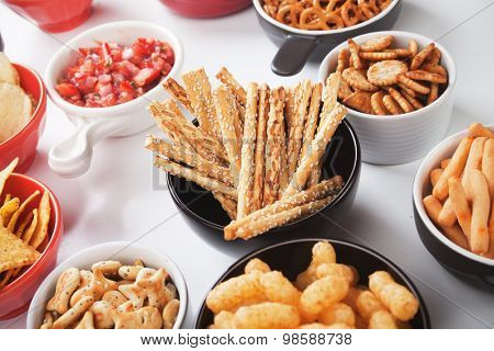 Salty grissini sticks with sesame seed and other savory snack