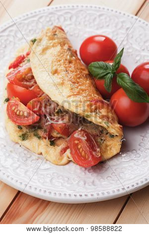 Omelet with cheese and cherry tomato served on a plate