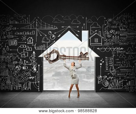 Young businesswoman and lifting big key above head