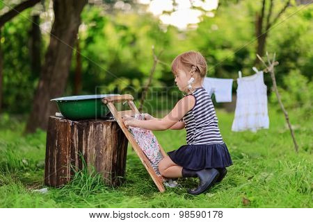 Little Helper Girlwashes Clothes Using The Washboard Outdoors