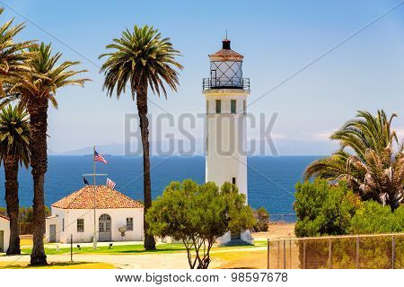 Lighthouse between palm trees against the sea