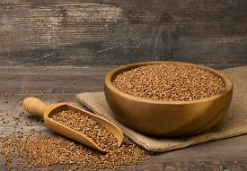 picture of buckwheat  - Buckwheat groats in a bowl and wooden scoop with buckwheat on grunge background - JPG