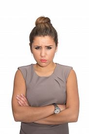 stock photo of frown  - An angry woman frowning with her arms crossed - JPG