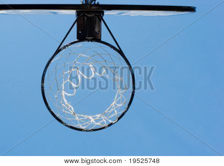 view of a basketball hoop from below, blue sky as a backdrop