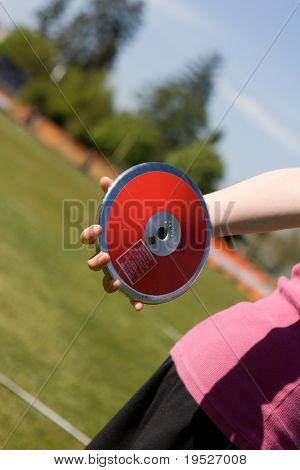 discus in hand with athletic field in background