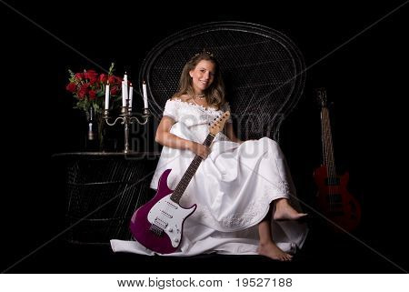 woman in bridal dress sitting on chair with guitars, roses, candles, & wine - black background