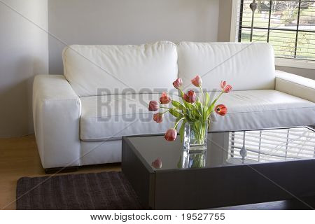 modern white living room with vase of red tulips
