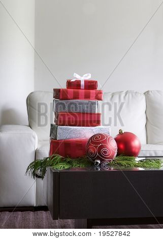 christmas presents and red ornaments on table in modern living room
