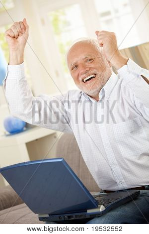 Old man celebrating at home, laughing and raising arms, having laptop computer, looking at camera.?