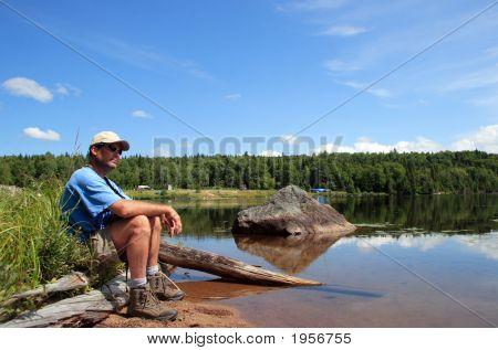 Relax Man Sitting Near A Lake In National Park