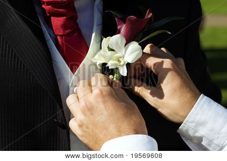 Best man places corsage on groom at weeding