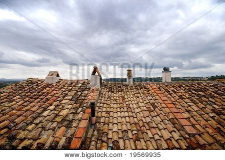 Terracotta rooftops of a traditional european village, looking out over brooding clouds