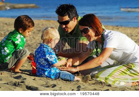 Young family playing at the beach in the morning sun...