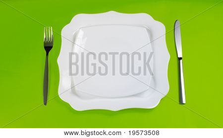 Knife, white figured and square plates and fork on green