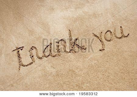 Thank you handwritten in sand on a a beach