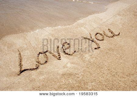 Love you handwritten in sand on a a beach