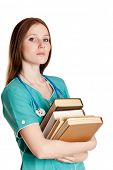 Portrait of serious female doctor in the green uniform with books.