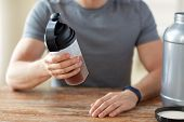 sport, healthy lifestyle and people concept - close up of man wearing fitness tracker with jar and b poster