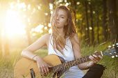 Stylish Female With Long Hair Relaxing At Sunlight In Beautiful Forest Playing Musical Instrument Wi poster