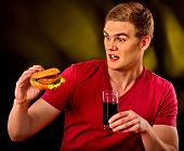Man eating french fries and hamburger. Student consume fast food on table. Man drinks cola and dream poster