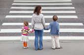 picture of pedestrian crossing  - young mother holds hand of his little daughter and son and standing near cross road - JPG