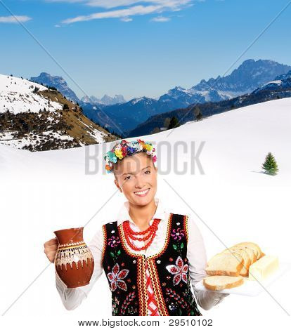 A portrait of a beautiful and hospitable Polish woman in a traditional outfit over mountain background
