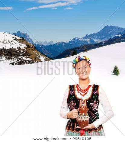 A portrait of a beautiful and hospitable Polish woman in a traditional outfit over mountains in winter