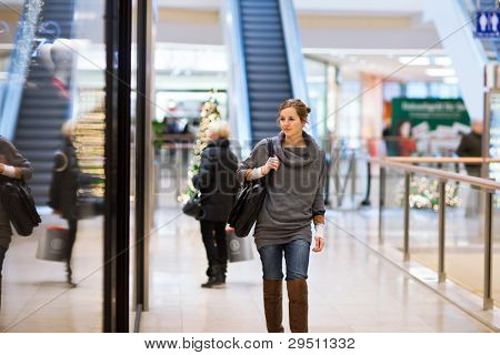 Young woman looking at store windows when shopping in a shopping mall/center