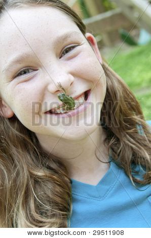 Happy girl with frog hanging from nose