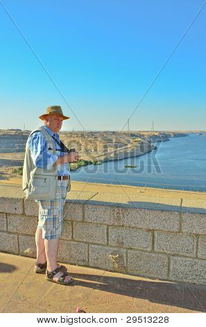 Senior tourist regarding Nasser Lake from Aswan Dam
