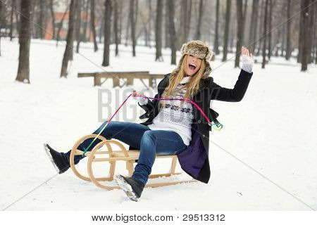 Outdoor Winter Portrait Of Happy Blond Young Woman On Sled
