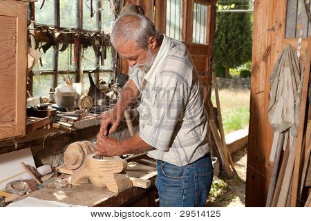 Old shed with a skilled carpenter working with wood