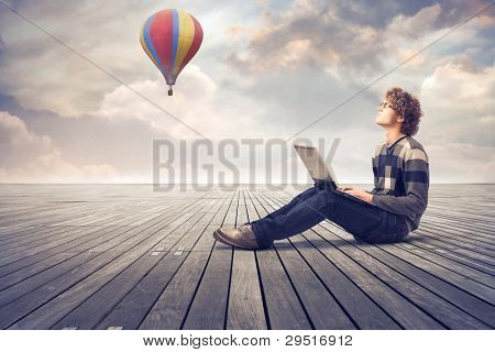 Young man sitting on a wooden floor and using a laptop with hot-air balloon in the background
