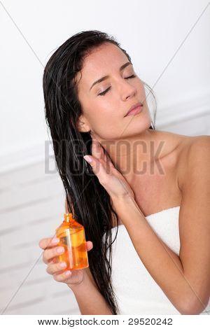 Atractiva joven sosteniendo la botella de aceite perfumado