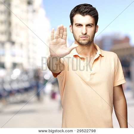 portrait of a serious young man doing a stop symbol against a crowded street