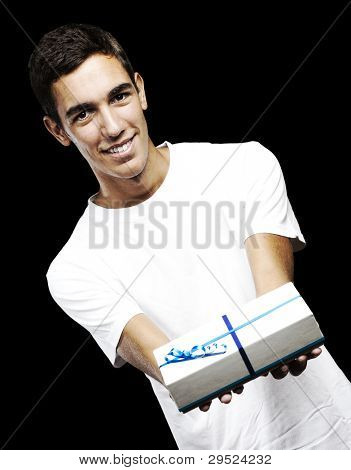 portrait of a young man with a gift against a black background