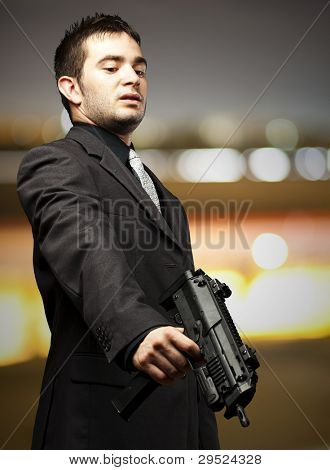 mafia man aiming down with a gun against a city by night